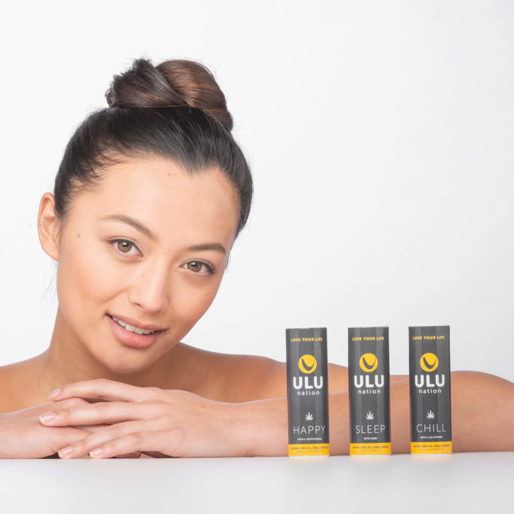 a girl with 3 ULU CBD Amino oil product tubes